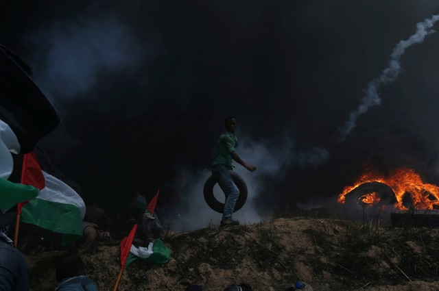 A Palestinian demonstrator carries a tire as others take cover from Israeli fire and tear gas during a protest against U.S. embassy move to Jerusalem and ahead of the 70th anniversary of Nakba, at the Israel-Gaza border in the southern Gaza Strip May 14, 2018.