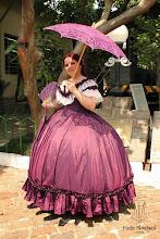 """Photo: Vestido """"Early Victorian"""" ( 1860 ) em tafetá violeta com rendas e babados. Era das crinolinas, a partir de R$ 600,00.  Underwear: Chemise e bloomer, corset midbust vitoriano ( 1860 ), crinolina em barbatana de aço rebitada e anáguas para crinolinas."""