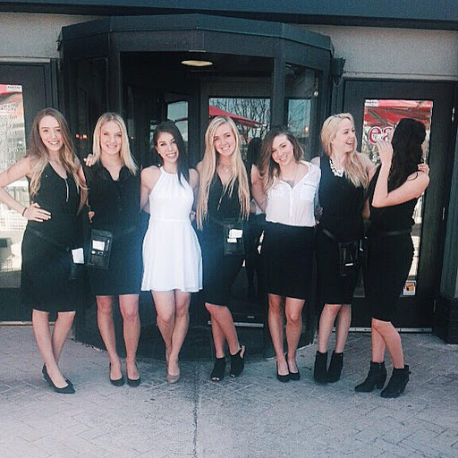 A group of servers standing in the entrance of their restaurant.