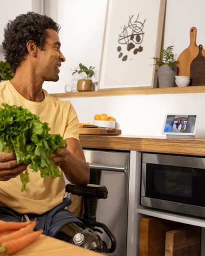 A man in a wheelchair cooks a meal on a stove while interacting with friends on a Nest Hub on the kitchen counter.