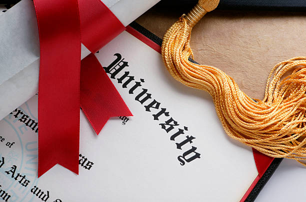 Gold tassel and rolled diploma with red ribbon A red ribbon wrapped around a rolled up diploma sits on top of a another college diploma.  A gold tassel from a graduation cap is also draped across the diploma. university degree stock pictures, royalty-free photos & images