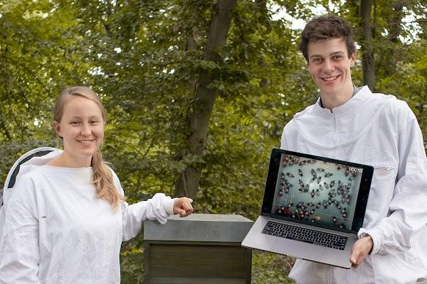 Katharina y Frederic de pie frente a una colmena, con videos de la cámara en una computadora