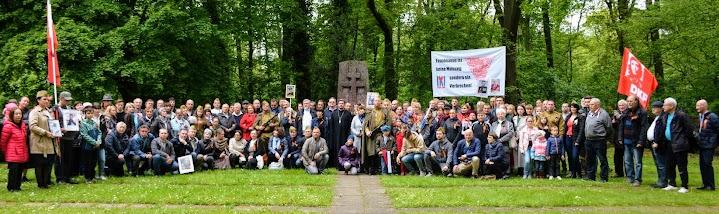 Menschen an der Gedenkstätte, rote Fahnen, Transparent: «Faschismus ist eine Meinung sondern ein Verbrechen».