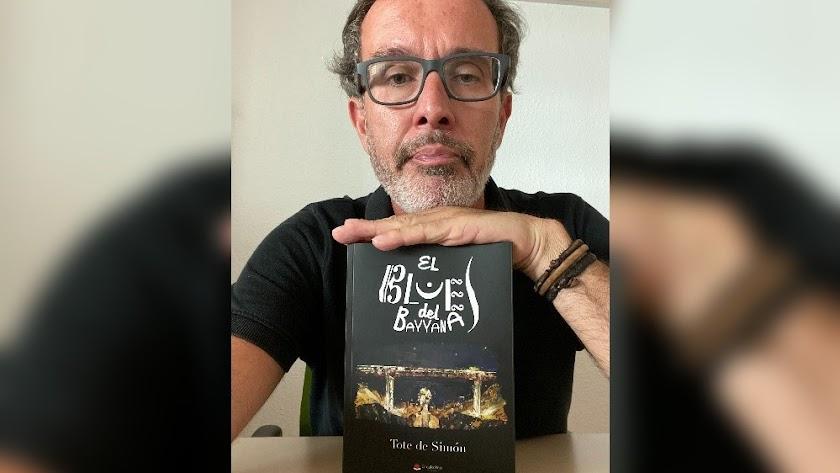 Tote de Simón con un ejemplar de su primer libro editado, El blues del Bayanna.