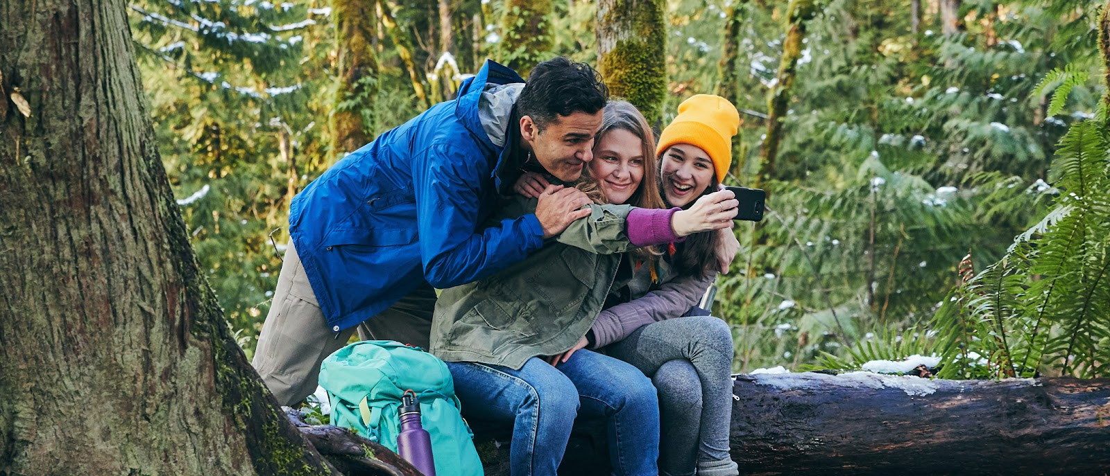 Three people huddled together taking a 'selfie' photograph