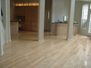 Photo: diagonal hardwood installation over cement floor with poles and islands to go around.