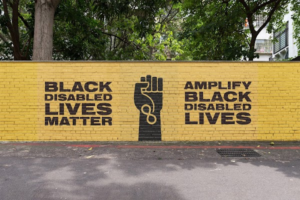 "A yellow brick wall painted with the phrases ""Black disabled lives matter"" and ""amplify black disables lives"" in black."