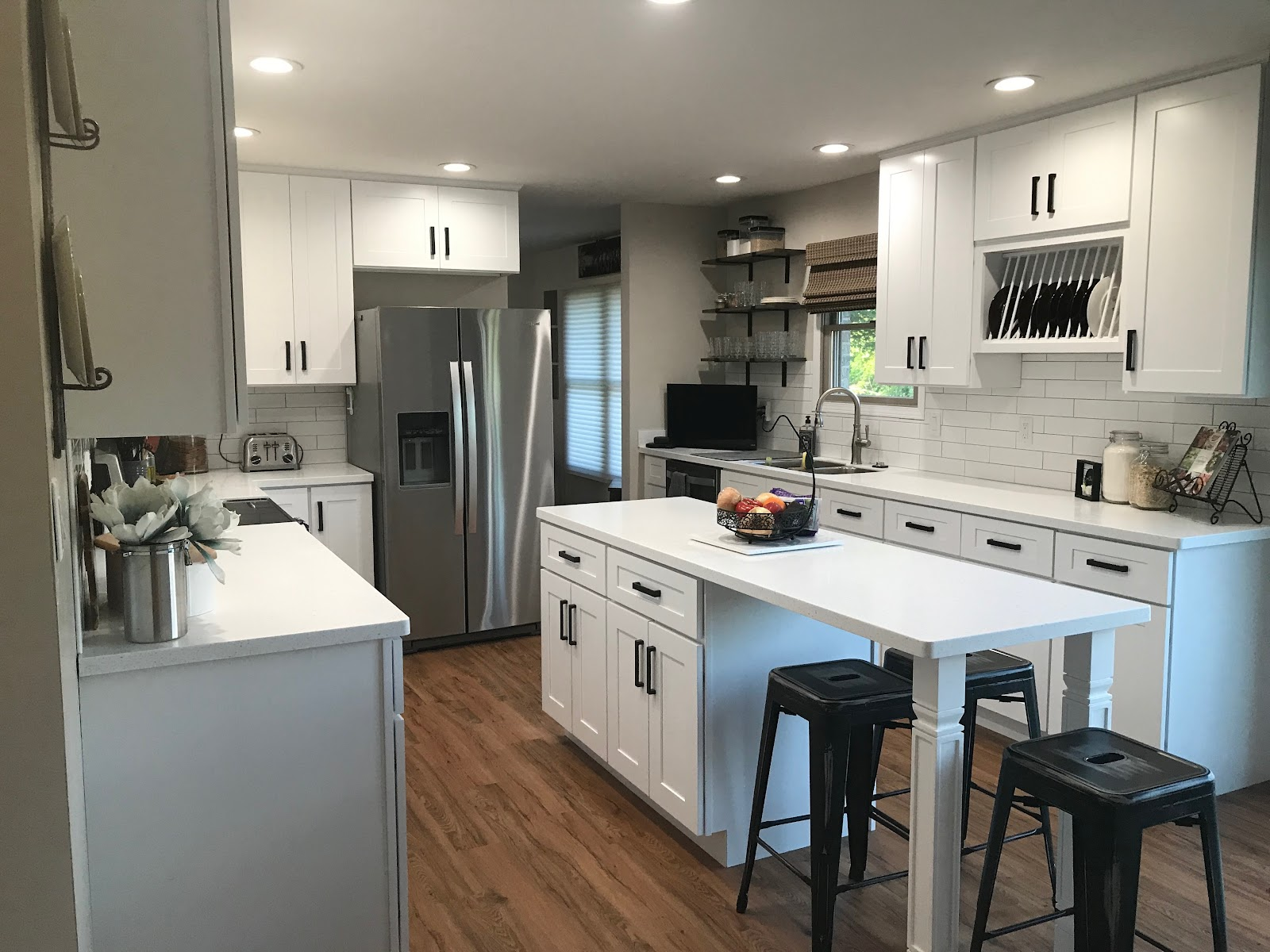 white shaker cabinets kitchen with matte black hardware and wood floors. a small center island with white countertops and black barstools match the kitchen design scheme