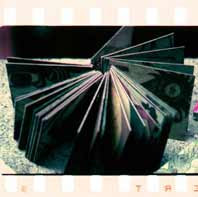 """Photo: original cut board plates bound with copper rings into a """"book"""" The plates are double sided, slightly smaller then a quarter sheet of letter paper."""