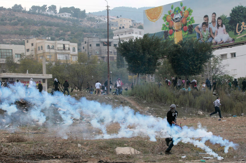 Photo: Palestinian stone-throwers run away from tear gas fired by Israeli border policemen.