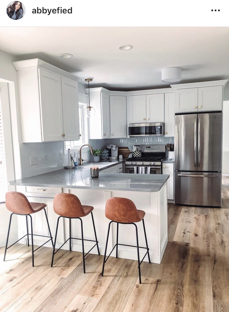 traditional kitchen remodel with white shaker cabinets, grey countertops and grey backsplash. wood floors and leather barstool chairs warm up the space
