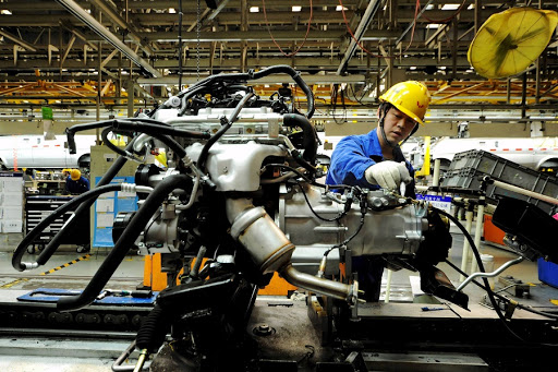 An employee works on an assembly line at a factory in Qingdao, China. Picture: REUTERS