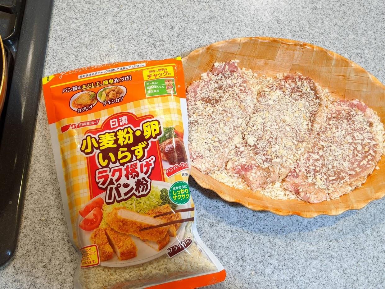 左にラク揚げパン粉のパッケージ 右に木目調の大皿にとんかつ用肉を3枚パン粉に付けて置いている画像