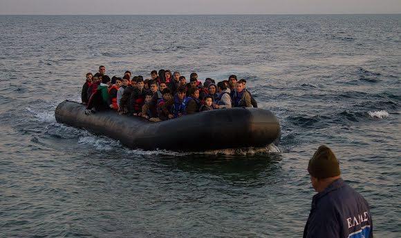 Un bateau transportant des réfugiés syriens arrive sur la côte tandis qu'un intervenant sur le terrain attend pour les accueillir.