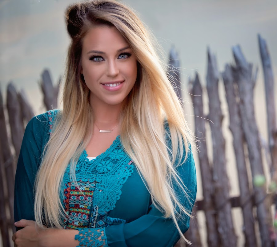 Happiness by Carole Brown - People Portraits of Women ( fence, teal shirt, blonde hair, gorgeous, green eyes, smiling )