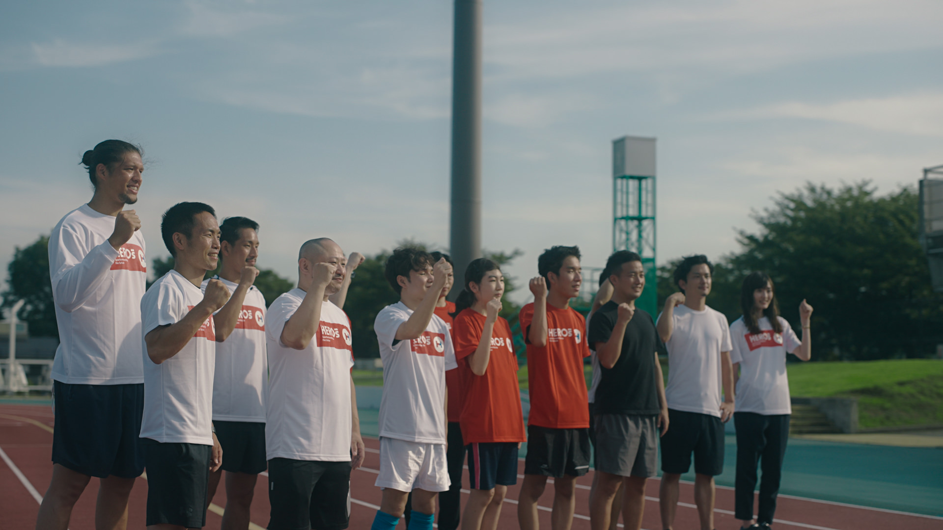 写真:Hero's Project のTシャツを着てポーズをしながら笑顔で集合写真を撮る13名のテスト走者とスタッフ。