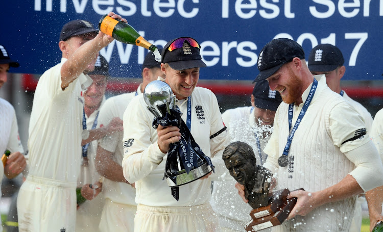 England captain Joe Root (c) and vice captain Ben Stokes with the trophy after day four of the 4th Investec Test match between England and South Africa at Old Trafford on August 7, 2017 in Manchester, England.