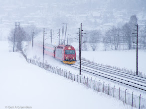 Photo: Norwegian State Railways (NSB) passenger train, pulled by EL18, running through snowy weather outside Drammen