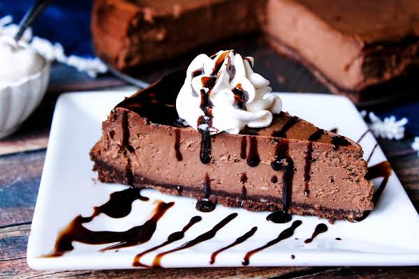 A Slice Of Chocolate Truffle Cheesecake With Whipped Cream And Drizzled Chocolate.