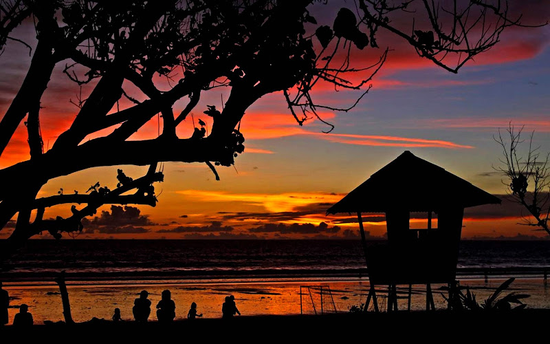 Sunset with locals and a hut overlooking a river in Bali.