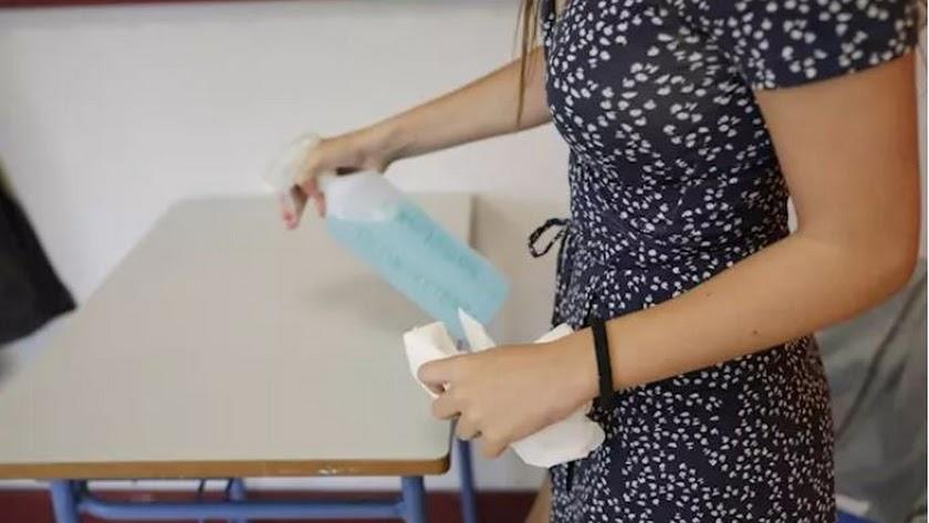 Una alumna desinfecta una mesa del Colegio Alameda de Osuna de Madrid.
