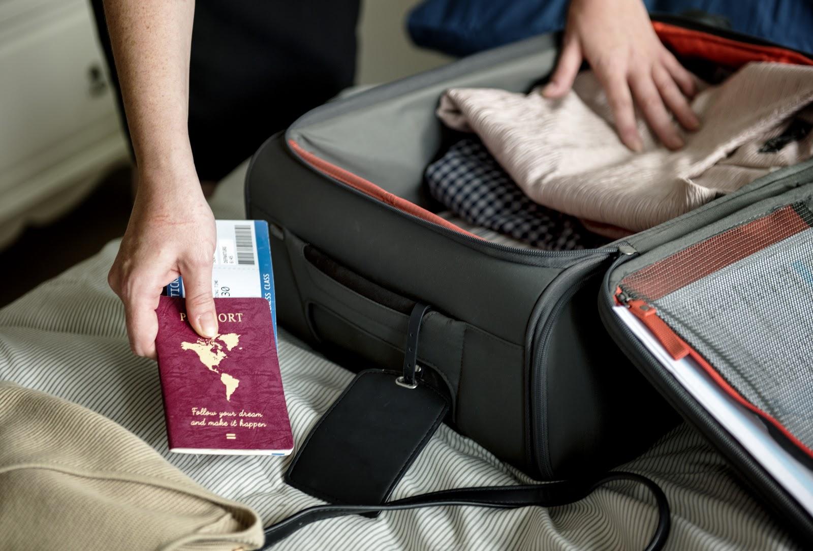 Pessoa arrumando mala com a sua passagem e seu passaporte em mãos