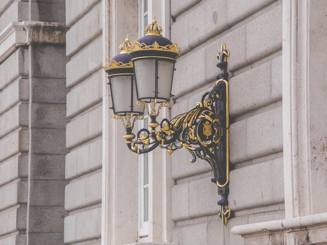 A beautiful light fixture on the outside of the palace that is black and gold