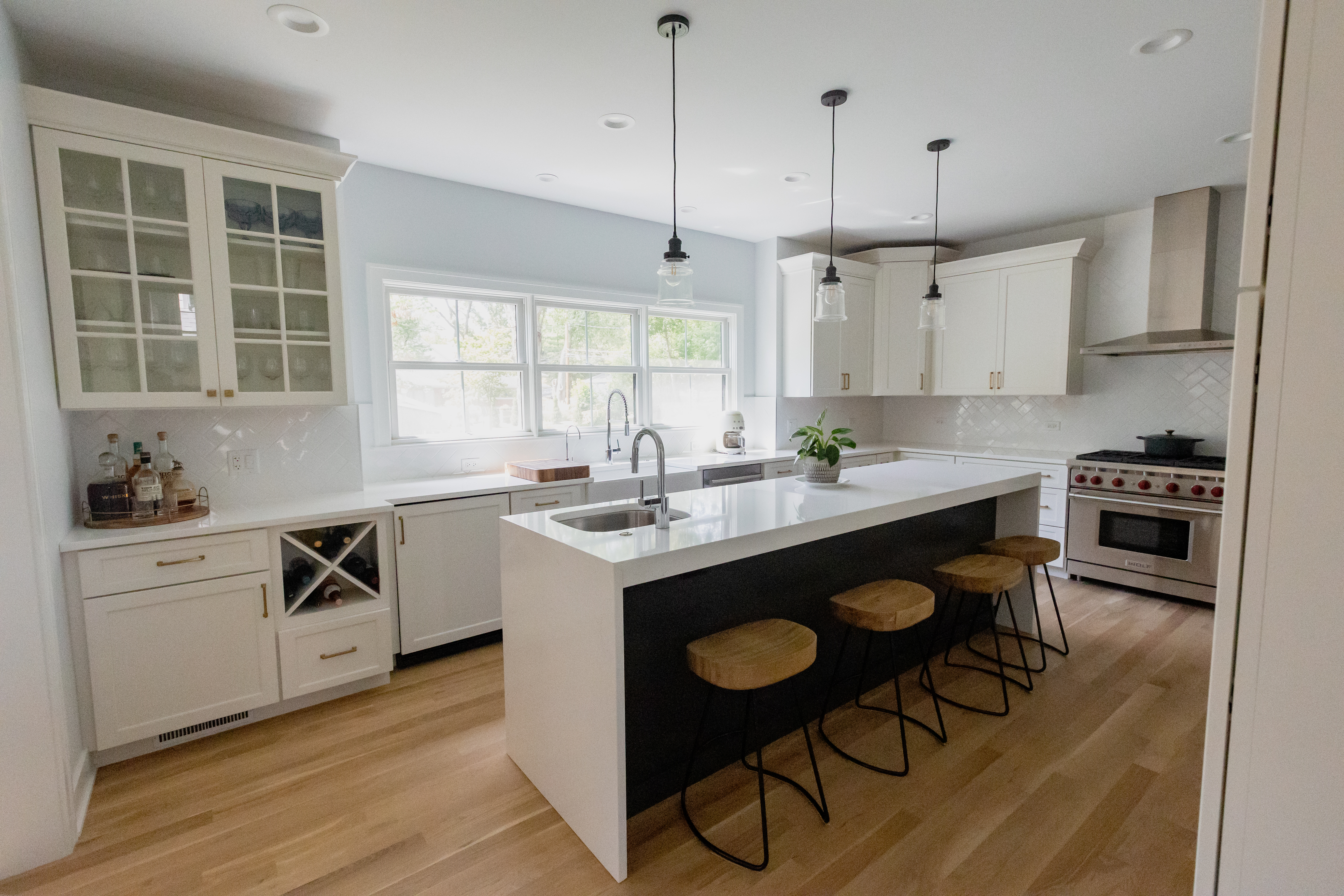 While kitchen with picture window over the sink and a eat-at center island featuring white cabinets and countertops with a dark gray contrasting island.