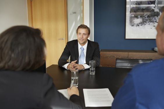 an interviewer sitting across the table facing two interviewers, one male and the other female.