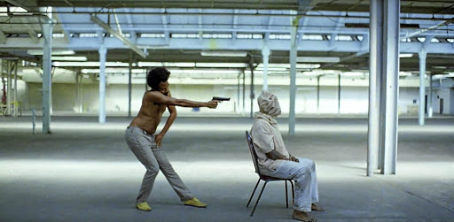 Donald Glover, as Childish Gambino, shoots a hooded man in a screen grab from his music video 'This Is America'.