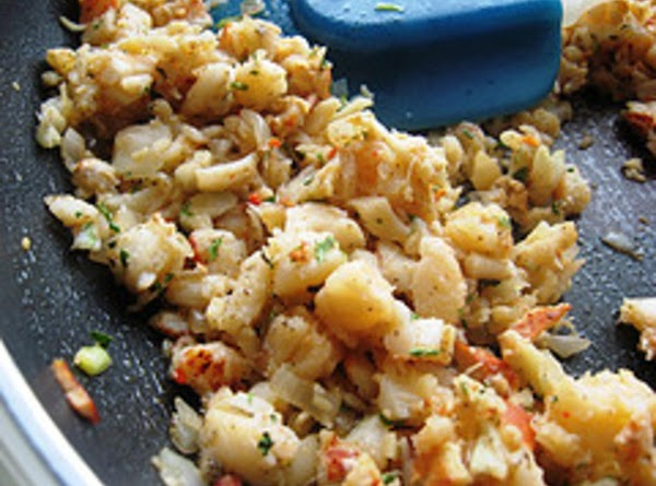 Lobster meat, shallots, parsley, and cheese mixed in a saute pan.