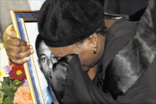 Janet Mohabe hugging a picture of her son, Prince Mohabe. The emotional funeral service was held at the local school and proceeded to Avalon cemetery. Prince and three others died after drag race went wrong. Pic: BAFANA MAHLANGU. 14/03/2010. © Sowetan.