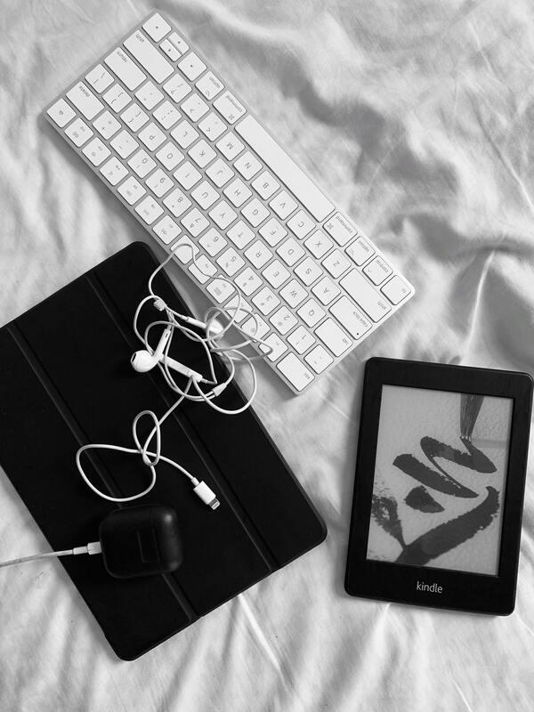foto de um teclado, fone de ouvido e kindle na cama