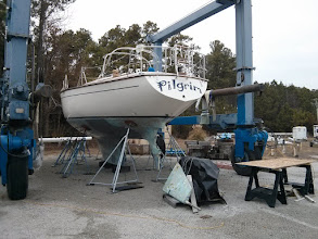 Photo: Tent removed from Pilgrim's bare hull. Note rudder leaning against engine in foreground. Definite sign of much work ahead when your rudder is leaning against your engine behind your boat on the hard.
