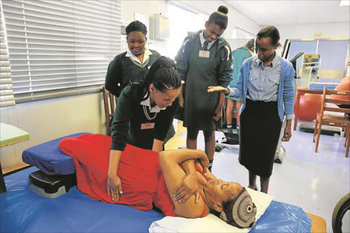 NEW SKILLS: John Bisseker Grade 11 pupils Khanya Nqwensio and Zizipho Dweba look on while their peer Roseline Adams helps patient Ntombencini Gqadushe, guided by physiotherapist Pakama Ramontseng. About 40 girls were shown how various departments in the hospital function and allowed to interact with patients Picture: ALAN EASON
