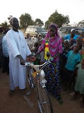 Photo: overhandiging van een fiets door de Chef du village