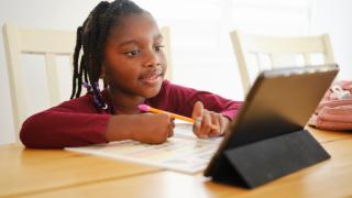 una niña haciendo los deberes mirando un tablet