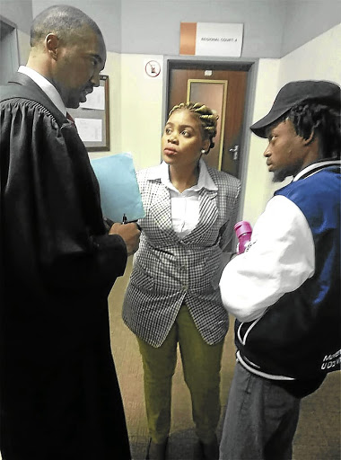 Attorney Asanda Pakade consults with Sibongile Mani, as Vusi Mahlangu, of Pasma and an Outsourcing Must Fall activist looks on. /MALIBONGWE DAYIMANI