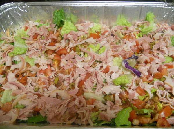 Layer until pan is full: salad mix meats (Ham, turkey, salami, bacon bits) cheese olives