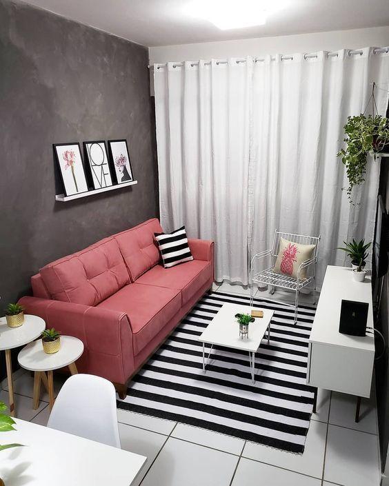 Sala com sofá rosa, tapete preto e branco, cortina branca longa, quadros decorativos.