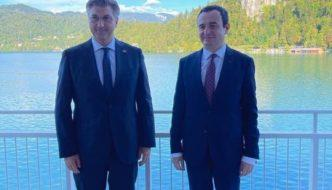 Two men in suits standing in front of a body of water  Description automatically generated with medium confidence