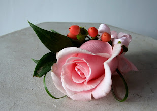 Photo: [B09] Bouttonniere of a single pink rose with pink hypericum berries, accented with Italian ruscus, and bear grass loops