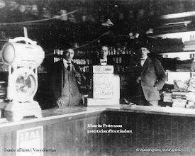 Photo: Affären i Vasselhytte byn 1920. 1896 fanns en affär i byn, den låg i en flygelbyggnad på Hanssons gård. Handlare var L-E Eriksson, senare övertog Bergling. I affären fanns även posten här ser man postföreståndaren i mitten, Mauritz Pettersson. 1920 hyrde Konsum lokalen av Hanssons.
