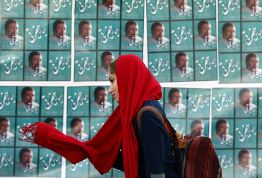 An Iranian woman passes an electronic election posters in Tehran, Iran. File Picture: EPA/ABEDIN TAHERKENAREH