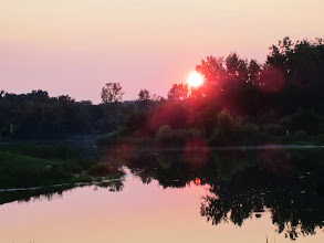 Photo: A red sun in a pink sky setting into a lake at Carriage Hill Metropark in Dayton, Ohio.