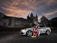vrouw voor grijze sportwagen, kasteel op achtergrond