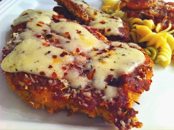 A Chicken Parmesan Topped With Melted Cheese And Red Pepper Flakes Sitting On A White Plate With Pasta In The Background.