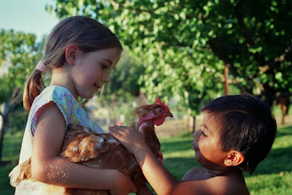 Photo: Mariah and Carlos (my sister and brother) play with one of our chickens. We always had hens mainly for their eggs, my parents still keep four or five even though they don't go through as many eggs with the kids out of the house.