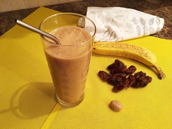 Shake In A Tall Glass With A Metal Straw Sitting On A Yellow Table Mat Along With Dates, Nutmeg, Banana And A White Napkin.