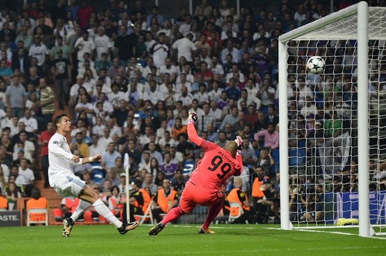Real Madrid's forward from Portugal Cristiano Ronaldo (L) scores a goal to APOEL Nicosia's goalkeeper from the Netherlands Boy Waterman that will be cancelled by line referee during the UEFA Champions League football match Real Madrid CF vs APOEL FC at the Santiago Bernabeu stadium in Madrid on September 13, 2017.